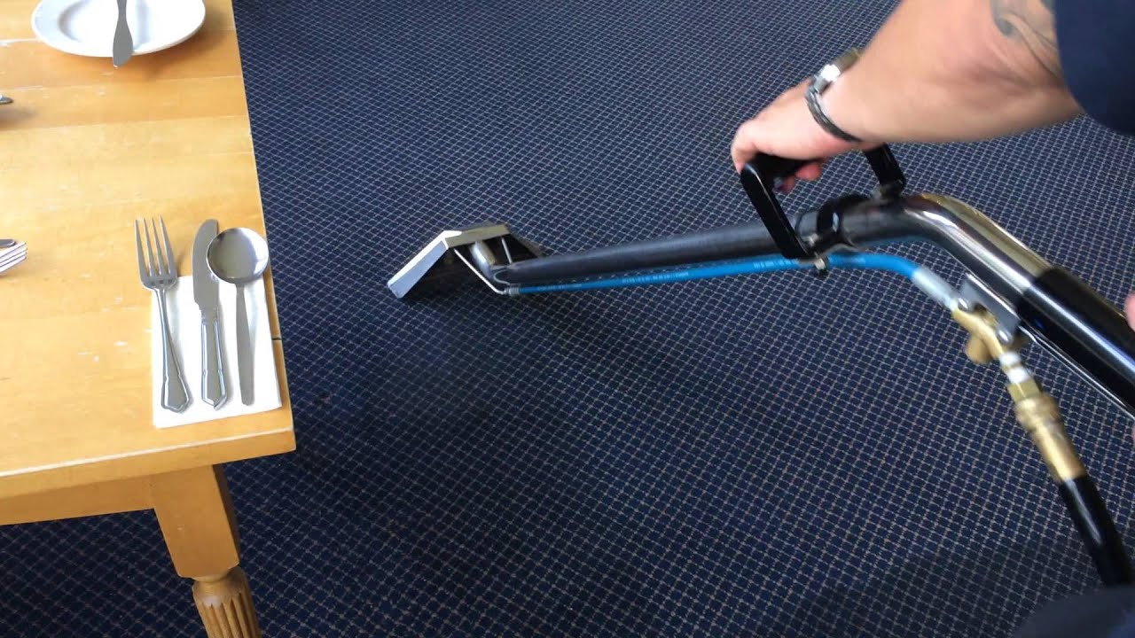 Steam Cleaning indigo color carpet with steam cleaner in restaurant showing a partial table on which fork spoon and a knife placed on white tissue and partial plate and spoon is also showing