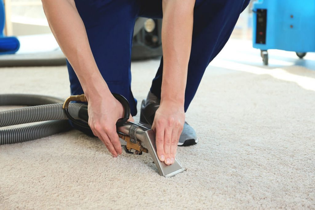 a boy is sitting on carpet and holding water extraction machine's nozzle on carpet tightly