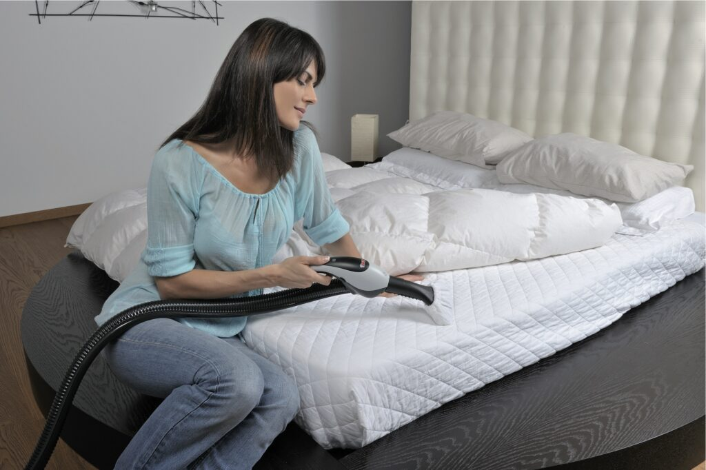 a beautiful young girl wearing sky blue color top and a jeans is sitting on white mattress and cleaning it with steam cleaner