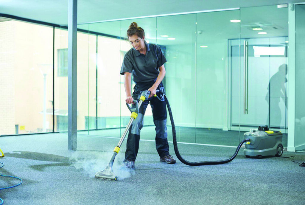 A girl cleaning carpet with steam cleaner In glass building